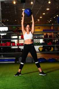 woman lifting blue and black weight ball